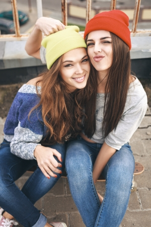 Two young  happy girl friends sitting together on longboard and having fun. Outdoors, lifestyle. photo