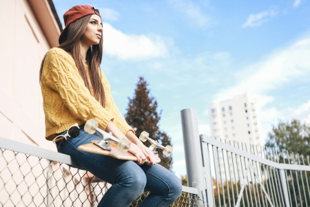 fashion girl: Beautiful young woman with  longboard sitting on the fence in the afternoon, outdoor