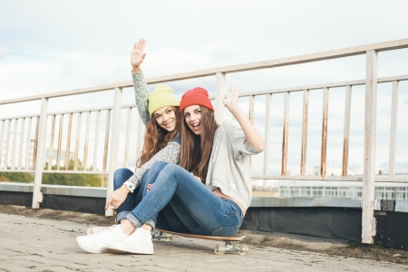 Two young  longboarding girl friends sitting together on longboard and waving hands. Outdoors, lifestyle. photo