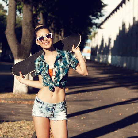 Trendy young girl in summer dress with skateboard. Outdoors. Urban lifestyle shot. photo
