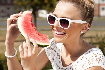 dieting: Jonge glimlachende vrouw neemt watermeloen van de geopende koelkast vol met groenten en fruit. Concept van gezond dieet en voeding Stockfoto