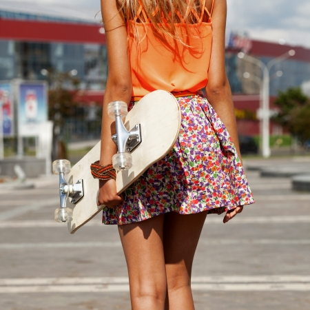 Funky Girl with skateboard walking on street. Urban style.\ View from the back. Outdoors, lifestyle
