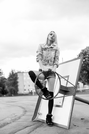 cool girl: Young beautiful woman having fun on the playground with a broken basketball backboard. Black and white. The girl in joyful feelings. Outdoors, lifestyle.