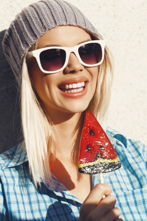 Young woman sucking a lollipop. Cheerful girl in sunglasses and a knitted hat have fun with candy in her hands. Licking candy. Outdoors, lifestile. photo