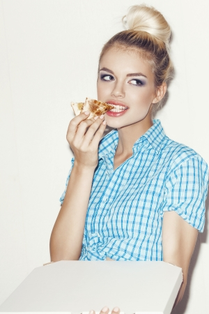 Young woman eating a piece of pizza. Indoors, lifestyle. photo