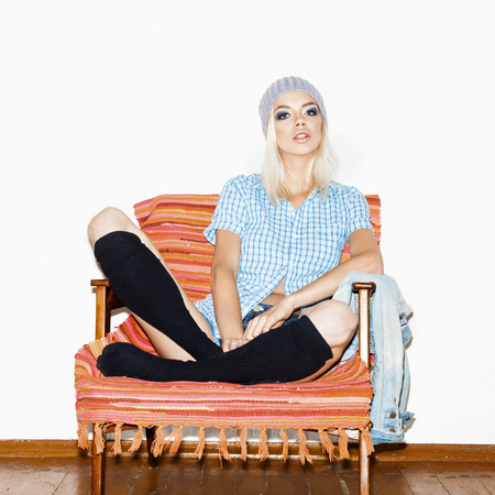 Beautiful young woman in a black socks and blue shirt sitting in armchair. Indoors photo