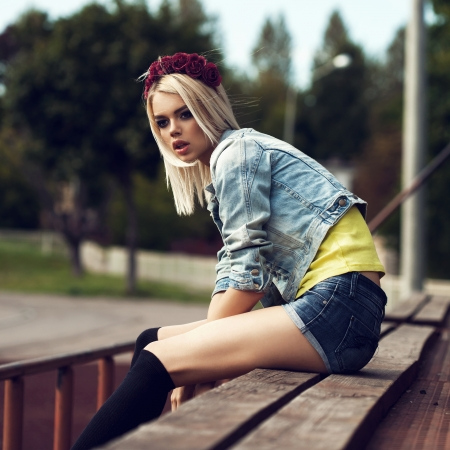 Beautiful happy woman relaxing outdoor. Pretty girl sitting in row of  wood  seats at school stadium. Rest from study. Outdoors, Lifestyle photo