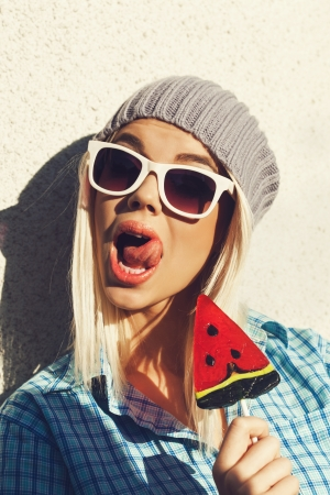 Young woman sucking a lollipop. Cheerful girl in sunglasses and a knitted hat have fun with candy in her hands. Lick mouth. Outdoors, lifestile. photo