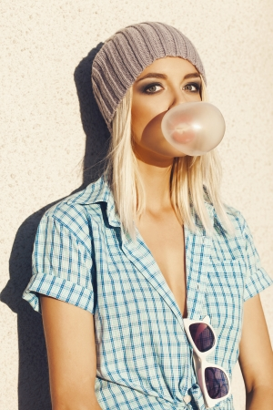 bubblegum: Trendy beautiful blonde  in grey knit hat and  blue shirt . Blow bubblegum. Outdoors, lifestyle.
