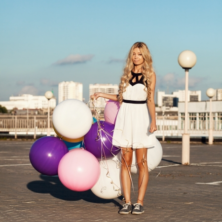 Sad young woman with colorful latex balloons.  Outdoors, lifestyle photo