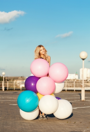 latex woman: Happy young woman smiling behind big colorful latex balloons. Outdoors, lifestyle