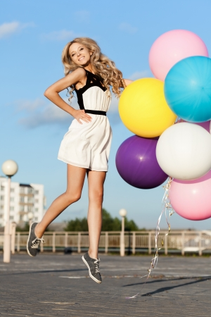 Happy young woman flying with big colorful latex balloons.  Gorgeous thick wavy hair. Outdoors, lifestyle Stock Photo