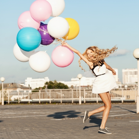 globos de cumpleaños: Mujer joven feliz que se divierte con globos de látex de colores. Gorgeous cabello ondulado grueso. Aire libre, estilo de vida