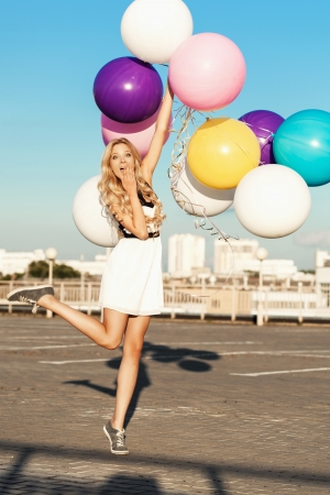 Happy young blonde having fun with big colorful latex balloons.  Gorgeous thick wavy hair. Outdoors, lifestyle