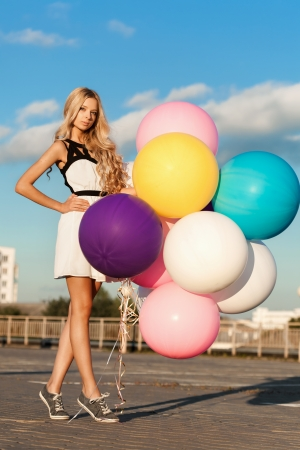 Happy young woman standing with  big colorful latex balloons.  Gorgeous thick wavy hair. Outdoors, lifestyle photo