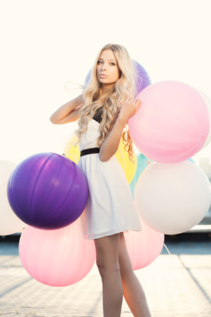 latex woman: Happy young woman with big colorful latex balloons against the evening sun going down. Outdoors, lifestyle