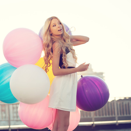 Happy young woman with big colorful latex balloons against the evening sun going down. Pastel colors. Outdoors, lifestyle photo