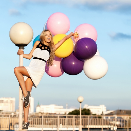 Happy young blond  woman with big colorful latex balloons. Beauty Romantic Girl Outdoors. Woman having fun on a lamppost on the background of blue sky.