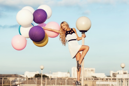latex girl: Happy young girl with big colorful latex balloons. Beauty Romantic Girl Outdoors. Woman  with long blond wavy hair  having fun on a lamppost on the background of blue sky.