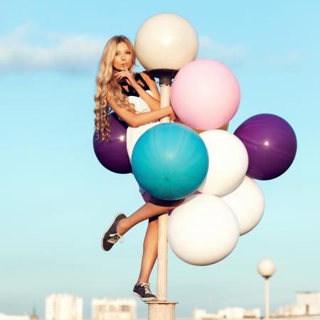 colores pastel: Feliz chica joven con grandes globos de l�tex de colores. Rom�ntico de la belleza al aire libre de la muchacha. Mujer enviar beso al aire sobre poste de luz en el fondo del cielo azul. Foto de archivo