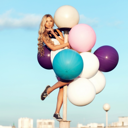 Happy young girl with big colorful latex balloons. Beauty Romantic Girl Outdoors. Woman send air kiss on lamppost on background of blue sky. photo
