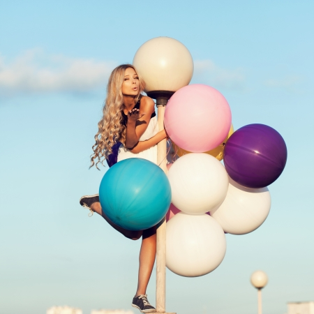 latex girl: Happy young girl with big colorful latex balloons. Beauty Romantic Girl Outdoors. Woman send air kiss on lamppost on background of blue sky.