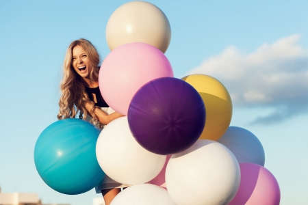 Happy young girl with big colorful latex balloons. Beauty Romantic Girl Outdoors. Woman smiling on lamppost on background of blue sky.