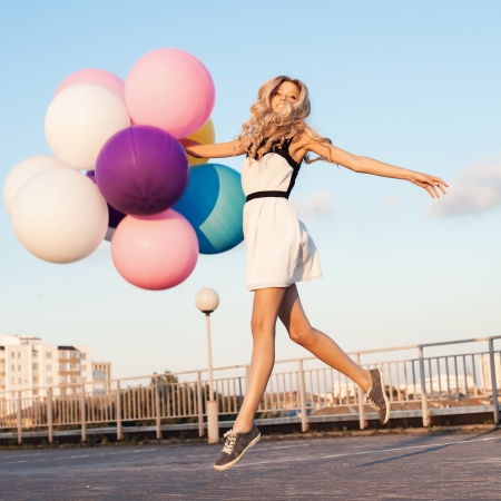Happy young girl walking with big colorful latex balloons. Beauty Romantic Girl Outdoors.