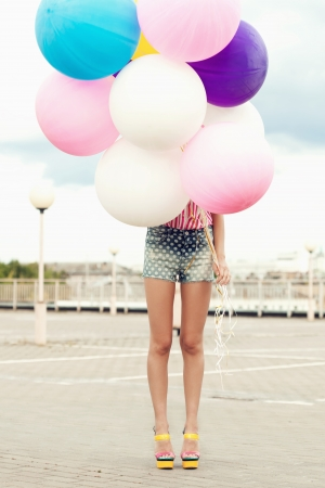 Happy young woman standing behind big colorful latex balloons. Outdoors, lifestyle photo