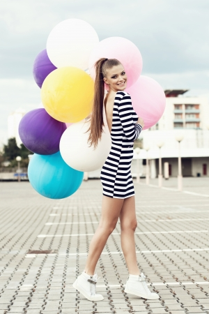 Happy young woman  with big colorful latex balloons. Outdoors, lifestyle photo