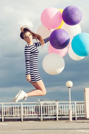 rayas de colores: Hermosa mujer joven feliz que salta con los globos de l�tex de colores. Aire libre, estilo de vida