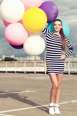 latex woman: Happy young beautiful woman with colorful latex balloons loking at camera. Outdoors, lifestyle