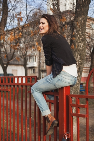 naughty woman: Portrait of a beautiful girl hipster. Trendy naughty woman sitting on the fence. Outdoors, lifestyle.
