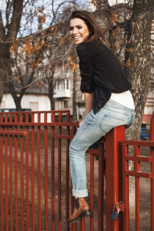 naughty woman: Portrait of a beautiful girl hipster. Trendy young naughty  woman sitting on the fence. Outdoors, lifestyle.