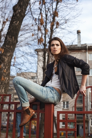 naughty woman: Portrait of a beautiful girl hipster. Naughty woman sitting on the fence. Outdoors, lifestyle.
