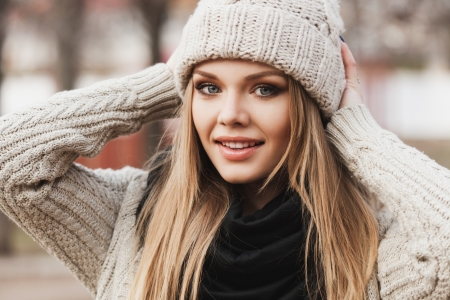 stylish girl: fashionable stylish girl in white beanie and knit jacket. Outdoors, lifestyle Stock Photo
