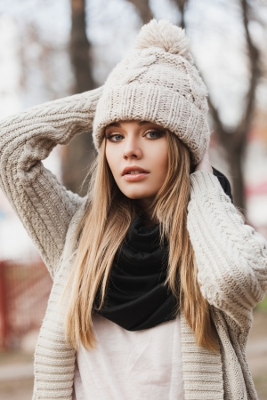 fashionable stylish girl in white beanie and knit jacket. Outdoors, lifestyle Imagens