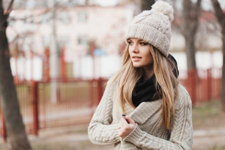 modieus stijlvol meisje in witte muts en gebreide jas. Buitenshuis, lifestyle