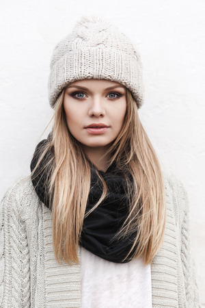 fashionable stylish girl in white beanie and knit jacket. Outdoors, lifestyle photo