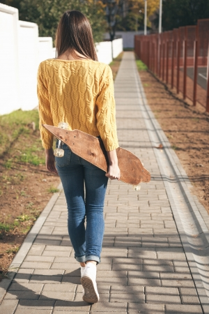 cool girl: Beautiful young woman  walking with a longboard in the afternoon. Skateboarding. Outdoors, lifestyle