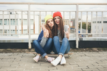 Two young  longboarding girl friends sitting together on longboard and having fun. Outdoors, lifestyle. photo