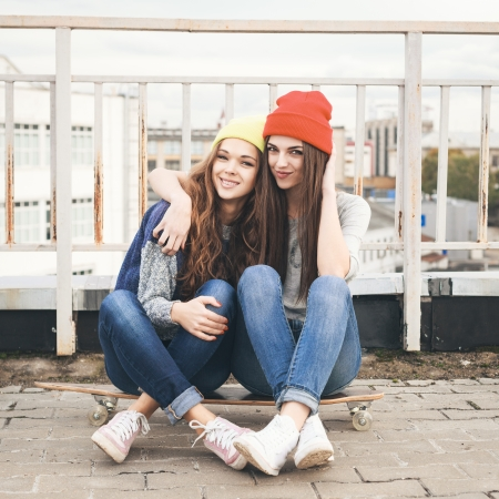 Two young girl friends sitting together on longboard and having fun. Outdoors, lifestyle.