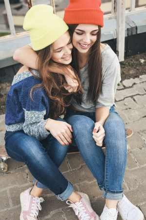 Two young girl friends sitting together on longboard and having fun. Outdoors, lifestyle. photo