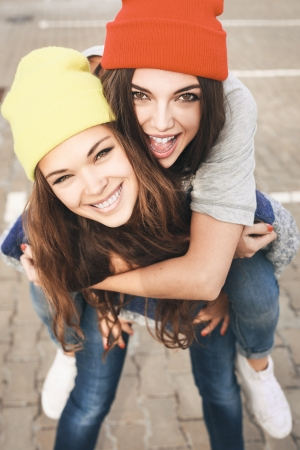 longboard: Two young hipster girl friends together having fun. Outdoors, lifestyle.