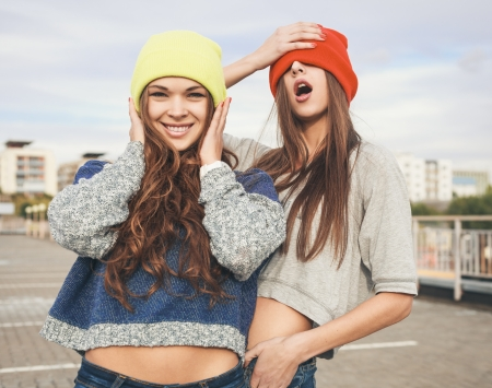 fun day: Two young hipster girl friends together having fun. Outdoors, lifestyle.