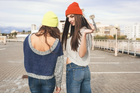 Two young hipster girl friends together having fun with skateboard. Outdoors, lifestyle. photo