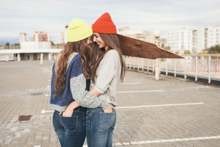 teen couple: Two young hipster girl friends together having fun with skateboard. Outdoors, lifestyle.