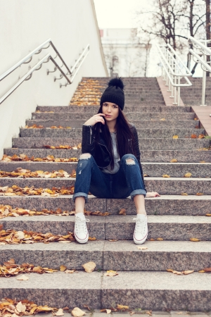 Portrait of a beautiful woman hipster. Teen girl sitting on stairs against wall. Outdoors, lifestyle. photo