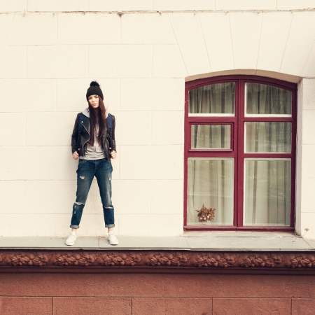 cornice: Young beautiful girl hipster standing  on cornice of house. Outdoors, lifestyle. Stock Photo