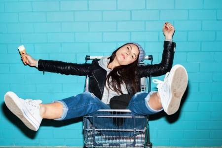 Young pretty woman holding ice cream over blue brick wall. Naughty girl having fun in shopping cart. Indoors, lifestyle photo